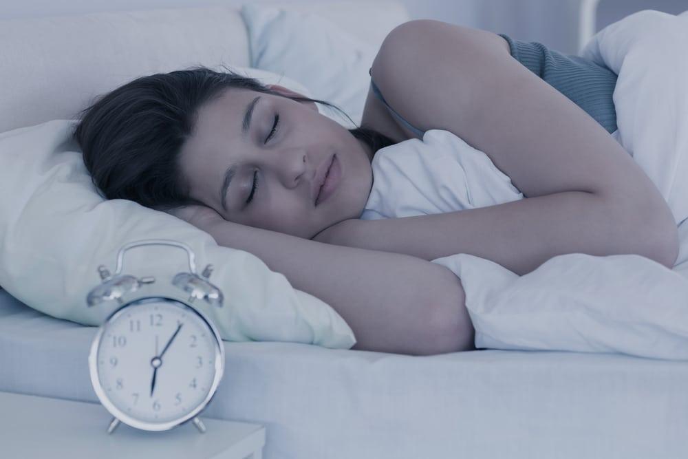brunette sleeping in her bed at home in the bedroom